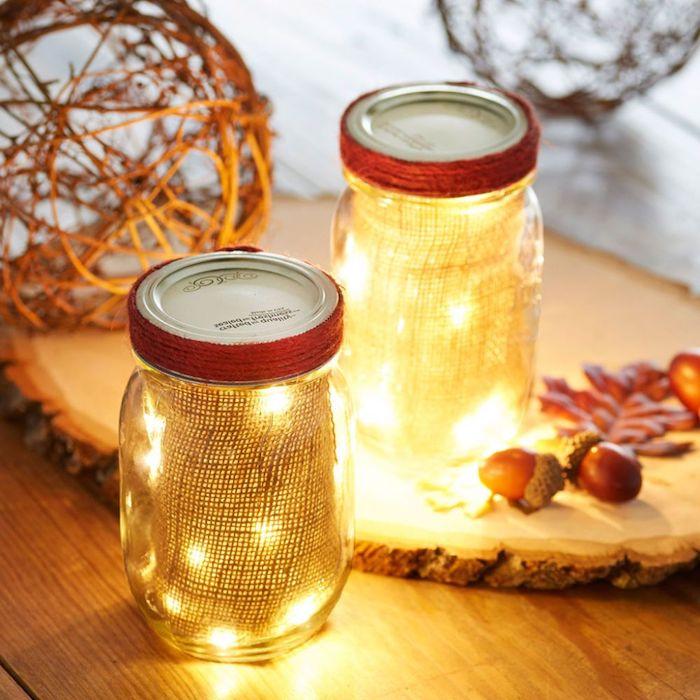 pots en verre décorés de jute et de guirlande lumineuse sur un rondin de bois avec deco feuilles mortes, glands et boule de brindilles