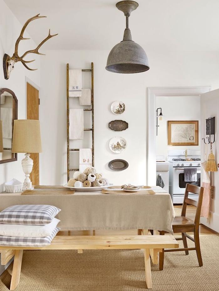 deco de charme dans une salle à manger en bois avec nappe grise, banc bois et echelle bois deco, suspension vintage campagne, deco murale en assiettes