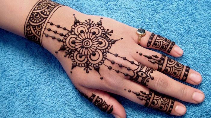 exemple de motif henné simple sur la main et les doigts de femme