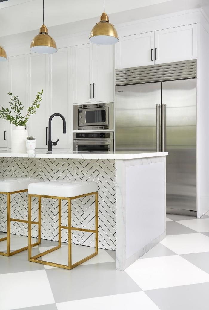 cuisine blanche moderne avec des électroménagers en acier inoxydable équipée d'un ilot central à façade en motif chevrons qui s'accordent parfaitement avec les accents en laiton