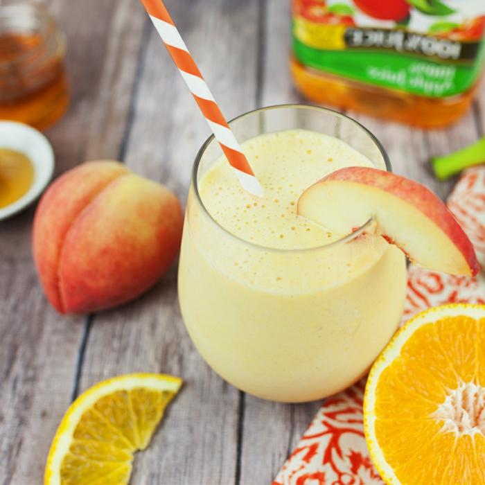 boisson crémeuse, smoothie avec pomme, pêche et banane garni de tranches d'orange