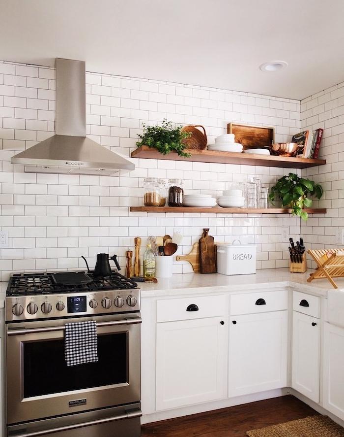 exemple de cuisine blanche avec four inox, étagères en bois surchargées de vaisselle et plantes, aspirateur en inox, parquet marron foncé