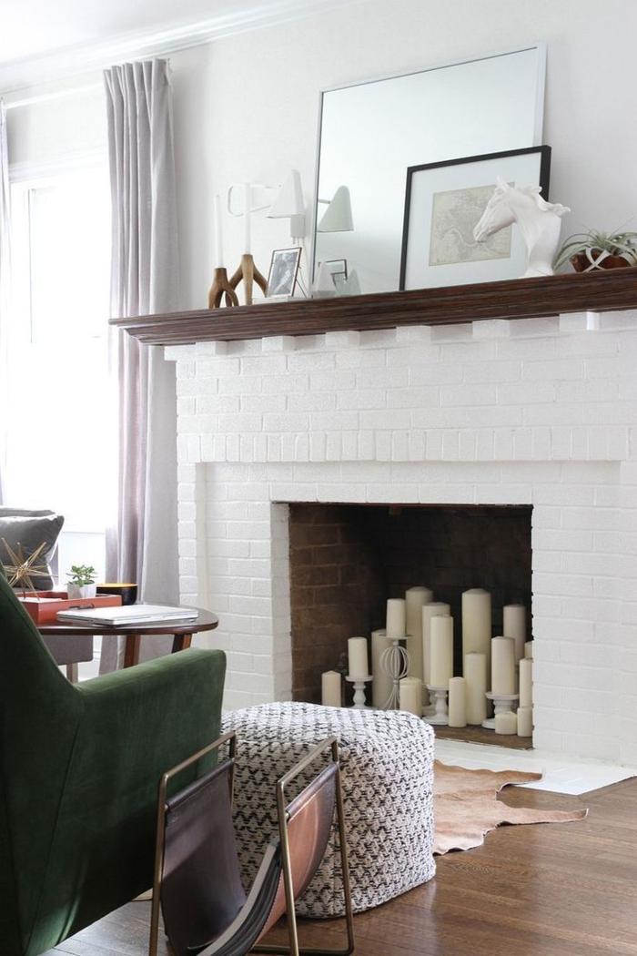 cheminée blanche, rayon de bois foncé, bougies blanches dans la cheminée, fauteuil vert