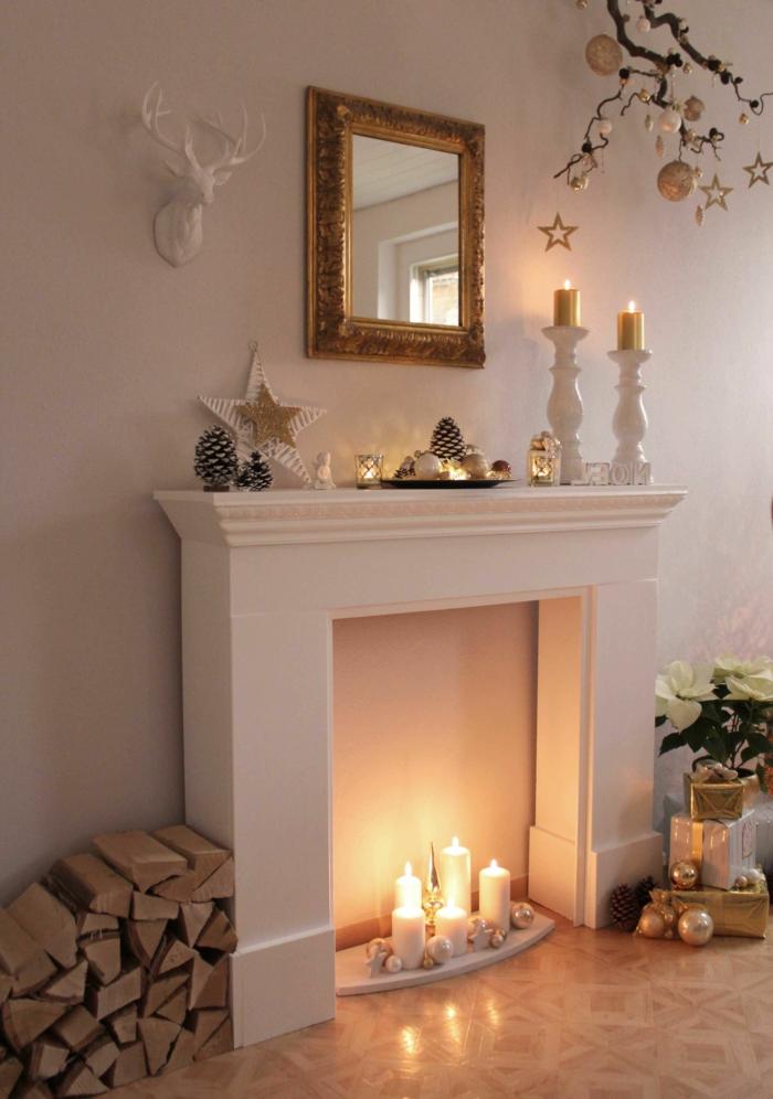 cheminée blanche, bougies blanches, miroir décoratif encadré, bûches stockés près de la cheminée