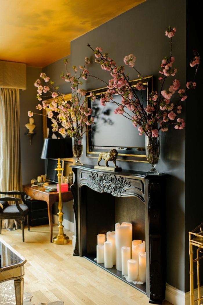 cheminée décorative noire, statuette lion, fleurs en vases, plafond jaune, meubles style baroque