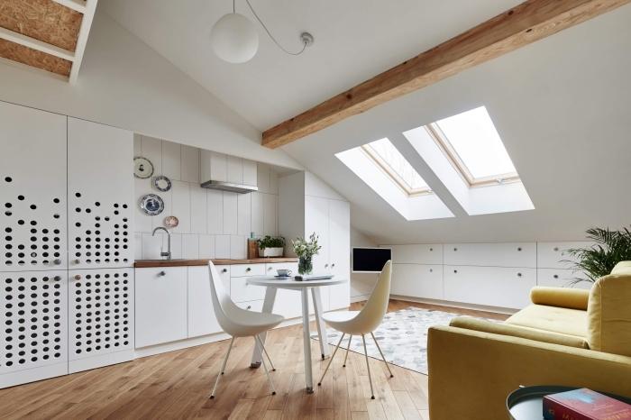 modèle de cuisine blanche ouverte aménagée avec meubles en bois et blanc, exemple comment décorer une pièce mansardée avec poutres en bois massif
