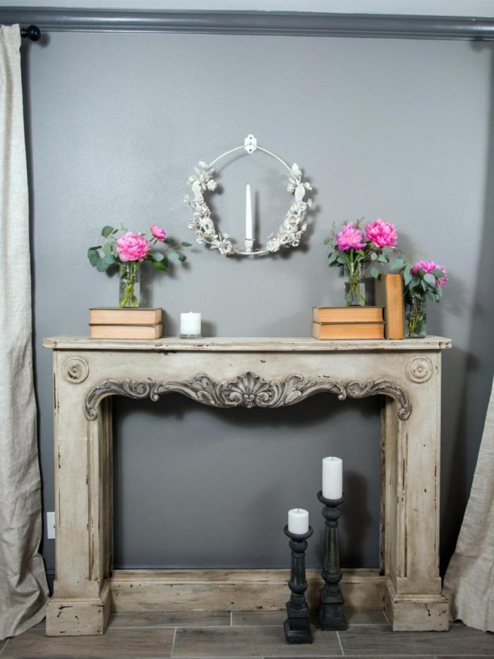 cheminée en bleu clair, livres et vases avec des fleurs, bougeoirs noirs, fausse cheminée