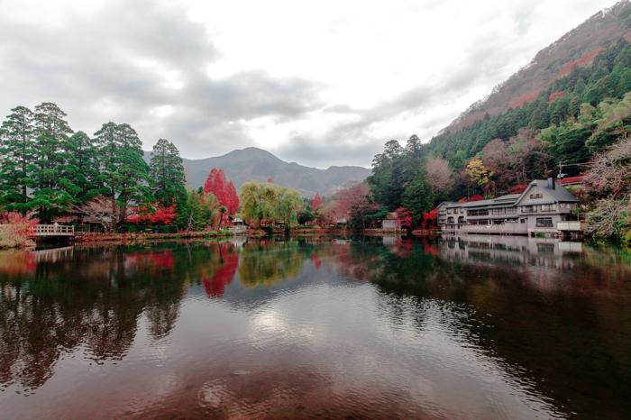 batiment blanc sous une falaise, rives de la rivière, feuilles des arbres touchées par l'automne