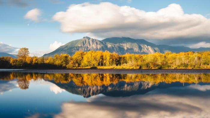 paysage d'automne, la foret qui se reflète dans les eaux du fleuve, montagne, grand nuage