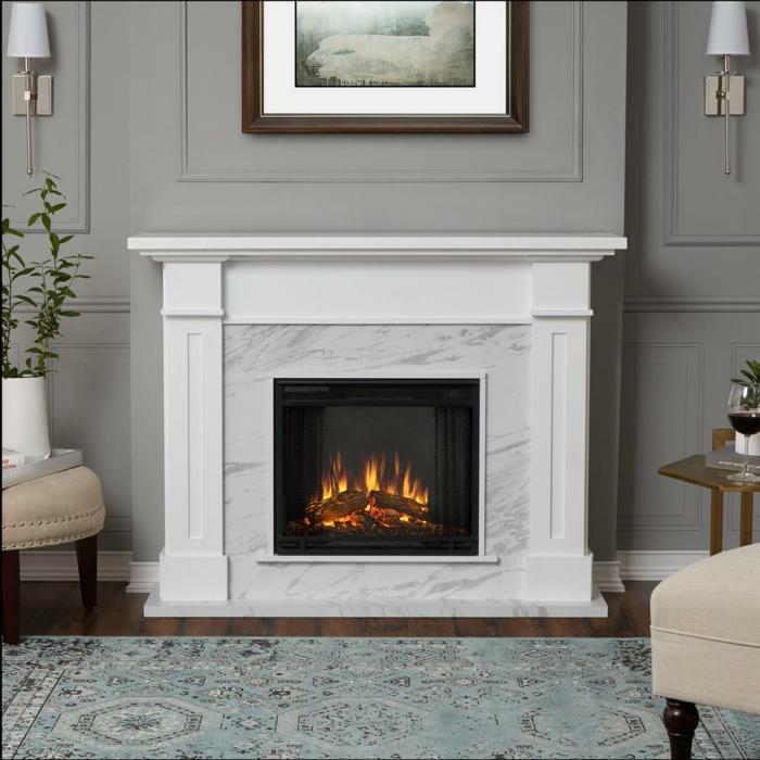 cheminée électrique à effet de flammes, tapis gris, chaise et tabouret crème, parement mural gris
