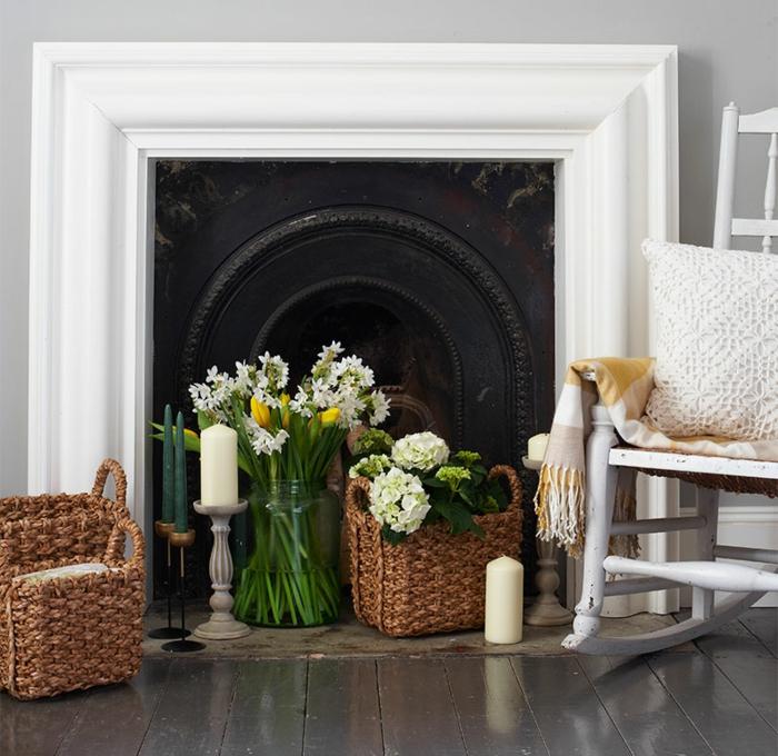 fleurs blanches en paniers rustiques, bougies blanches, chaise bercante près de la cheminée
