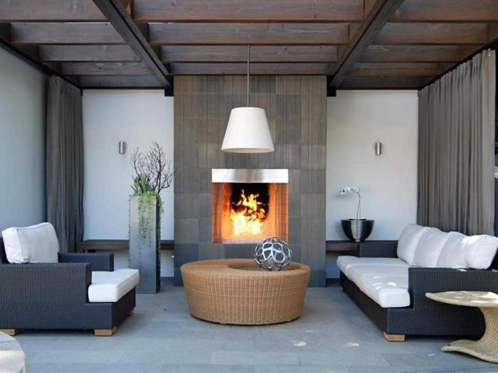 table basse ronde dans un salon gris, cheminée murale moderne, plafonnier blanc, poutres en bois