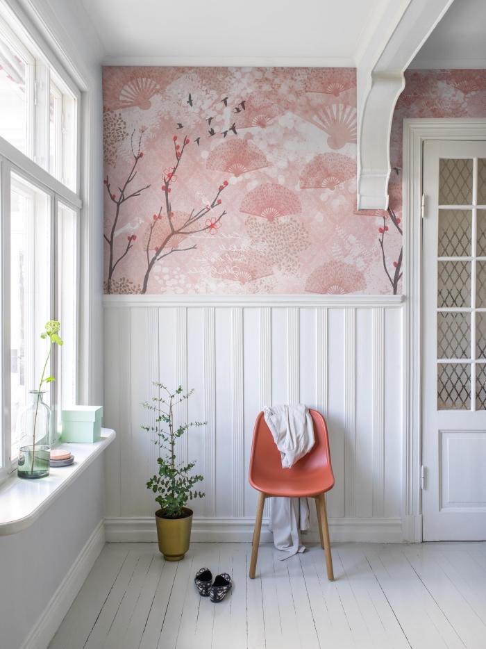 un mur recouvert à moitié de lambris blanc et à moitié de papier peint à motif japonais façon frise murale originale pour apporter de la douceur au salon ou à l'entrée