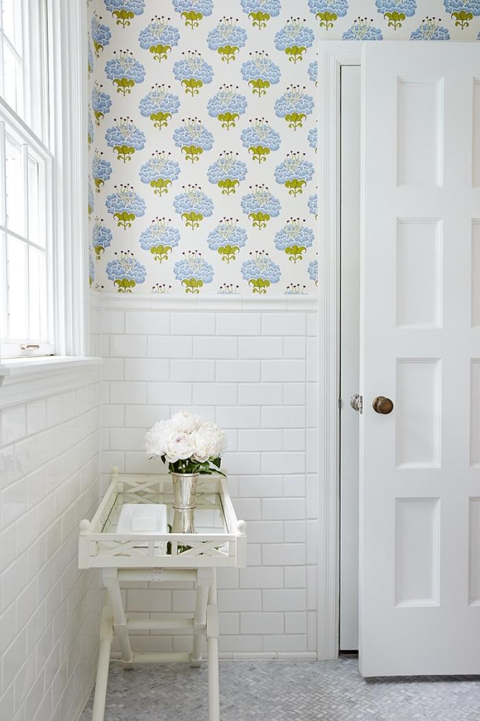 du papier peint toilette à motifs floraux bleu et vert posé en haut du mur pour rafraîchir l'intérieur blanc