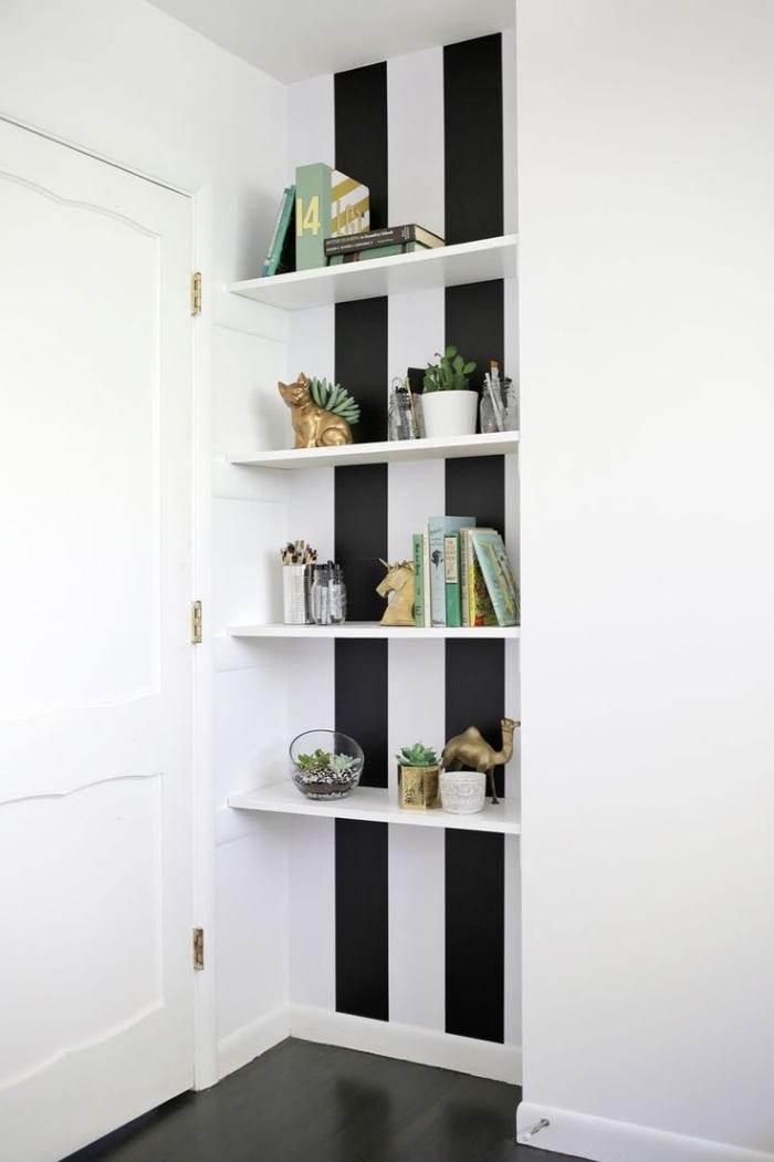 pose papier peint adhésif à rayures noir et blanc derrière une étagère ouverte pour créer un joli recoin déco en contraste avec les murs blancs