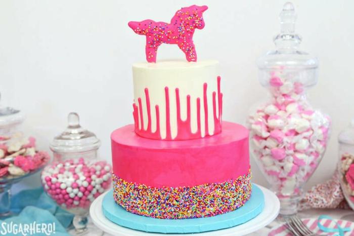 bocaux en verre remplis de bonbons blancs et roses, unicorne rose, gâteau de deux étages nappé de pâte à modeler