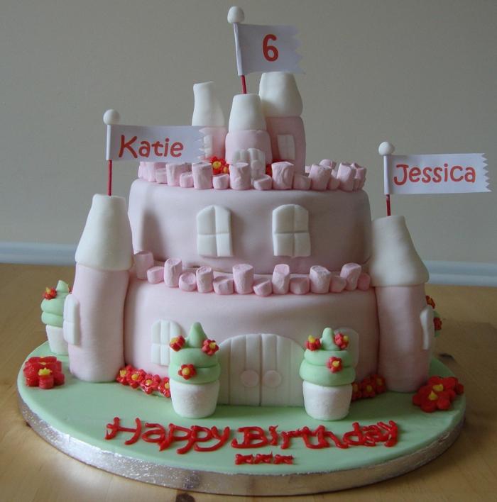 gateau rose chateau pour une fête de double anniversaire, tours roses avec drapeaux, scripts avec pâte
