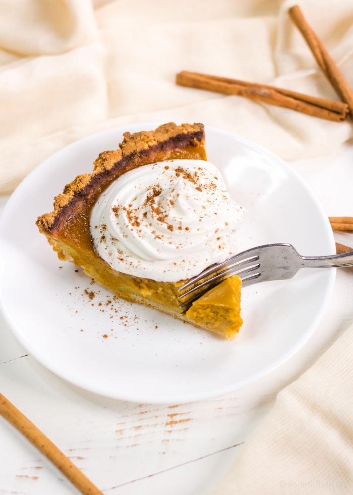 recette healthy de tarte à la citrouille sans gluten à la farine d'amande avec une garniture de crème fouettée, préparée avec cinq ingrédients et peu de sucre