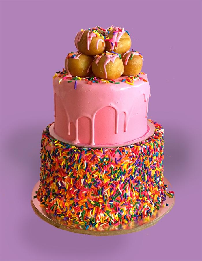 joli gateau creation, cake rose nappé de glaçage rose et des choux au top, déco pour pâtisseries