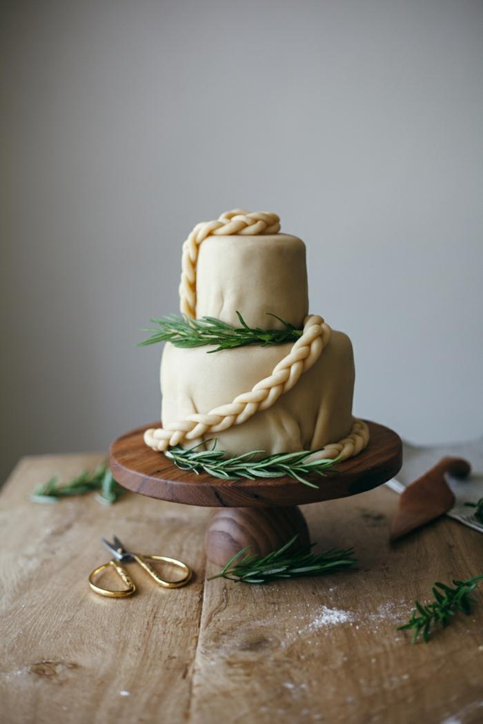 gateau mariage blanc super élégant, table en bois, ciseaux à anses dorées, décoration de brins de pin