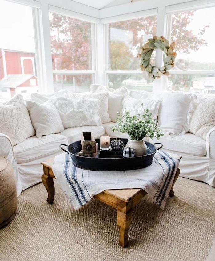 deco campagne dans un salon chaleureux avec canapé d angle blanc, table basse bois brut, centre de table fleurs, bougies et objets anciens