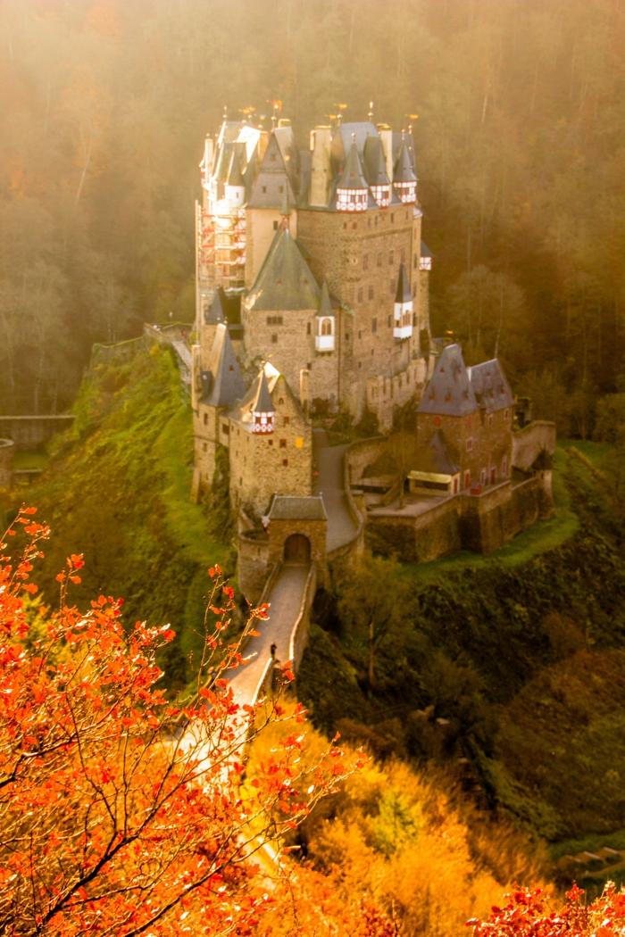 fond ecran paysage, chateau magnifique, pont, remparts, feuilles dorées d'un arbre qui donne sur le batiment