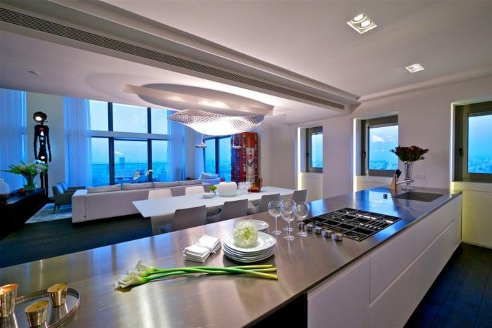separation cuisine salon avec un grand comptoir, plafond gris clair, salon avec mur vitrée et vue, grande table blanche, décor contemporain
