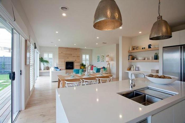 jolie idée cuisine ouverte, lampes loft, grand comptoir blanc avec évier, rayons muraux en bois