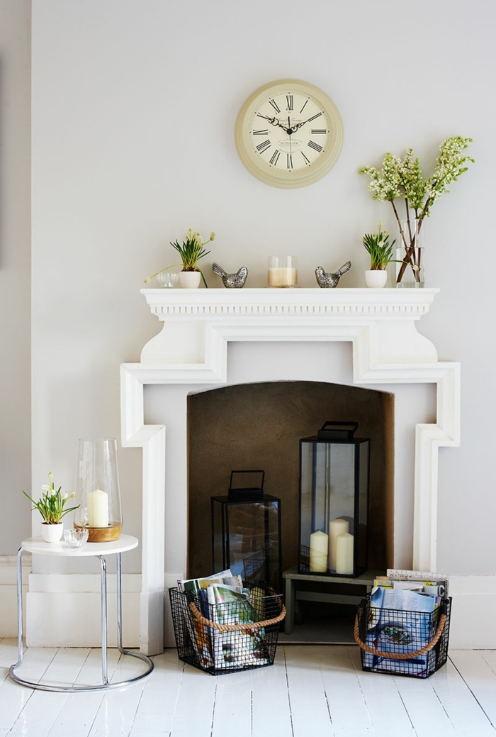 table basse blanche, cheminée blanche, grandes lanternes noires, horloge murale blanche, déco fleurs et bougies
