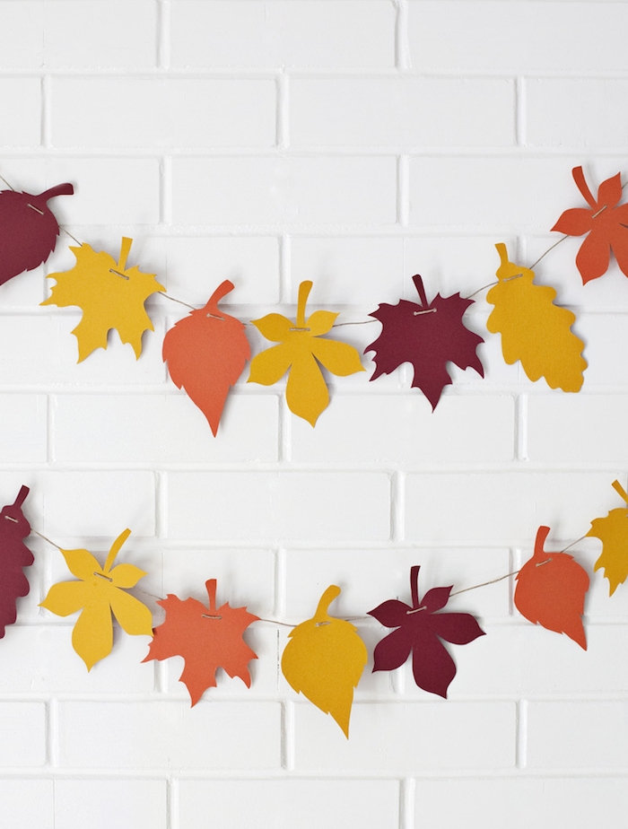 deco mur blanc décoré de guirlande en feuilles mortes papier jaune, orange et rouge, activité manuelle facile en papier
