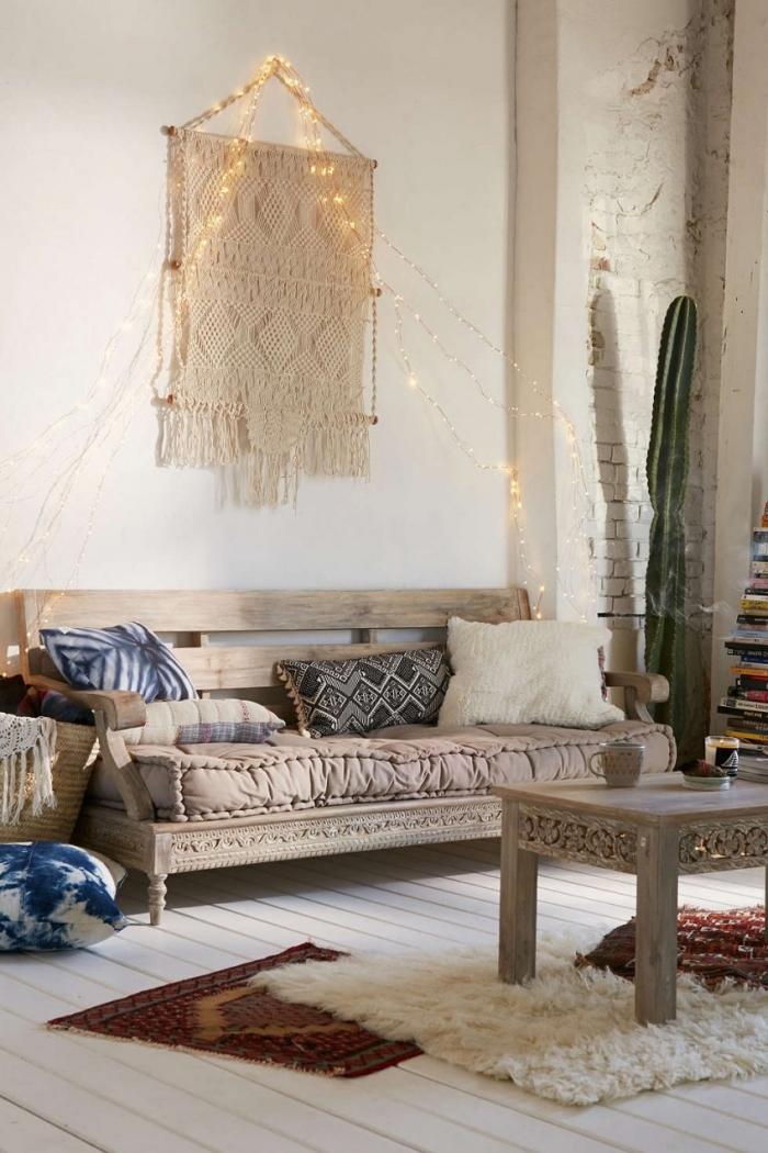 exemple de création murale en fil macramé, déco de salon bohème chic avec canapé de bois et coussins décoratifs