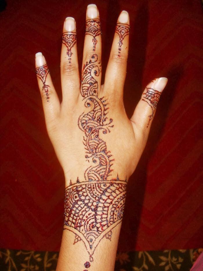 dessin au henné couleur marron cuivre sur la main et le poignet