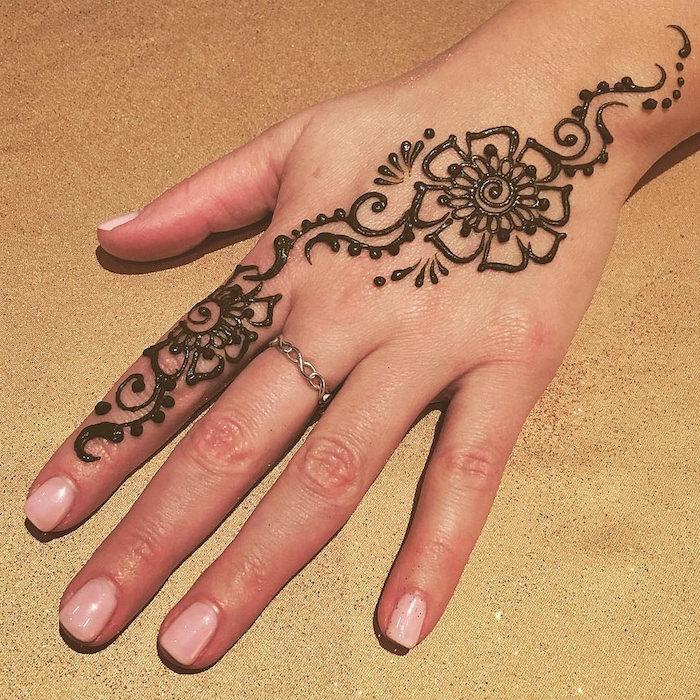 petit motif dessin au henné sur la main avec fleur sur le dessus