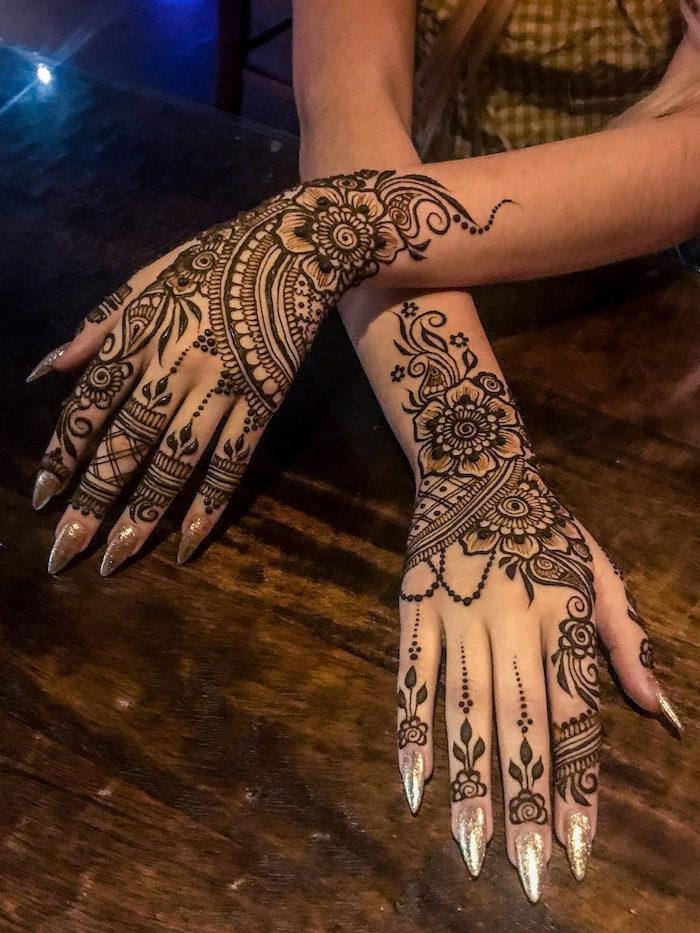 tatouage au henné noir détaillé avec fleurs et mandala sur mains et poignets