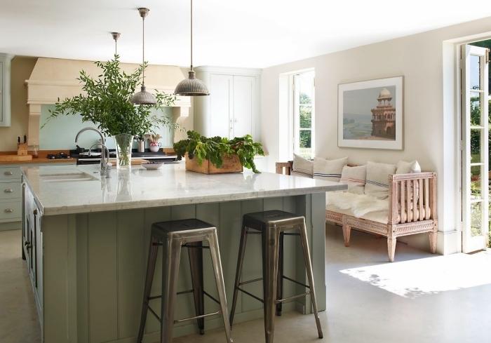 cuisine avec ilot central style campagne chic habillé de lambris peint en vert amande avec un comptoir en quartz blanc