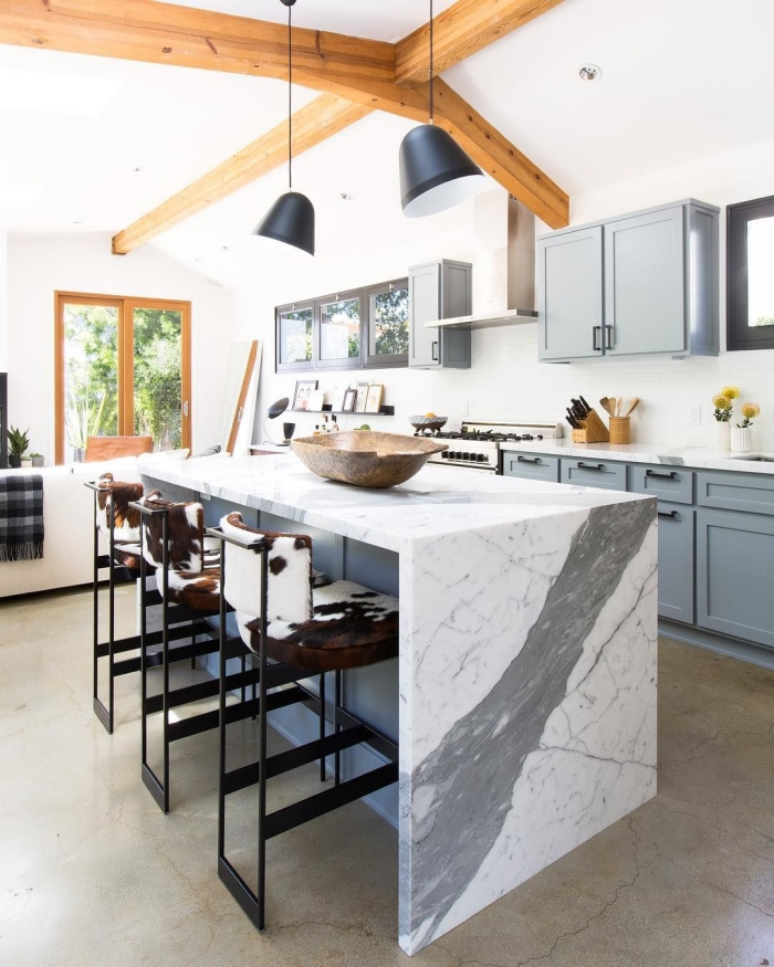 contraste fort entre l'ambiance rustique de la cuisine avec des poutres en bois et des armoires au design traditionnel d'une part et le plan de travail ilot central en marbre