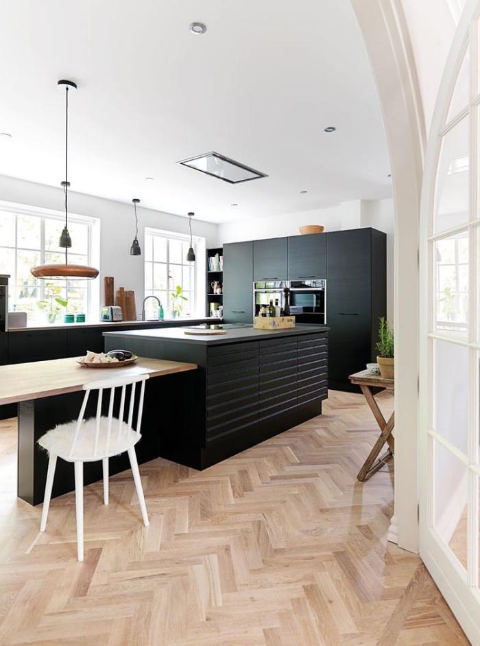 ambiance scandinave épurée dans cette cuisine aux armoires à finition noir mat qui s'organise autour de l'ilot central avec table en bois intégrée