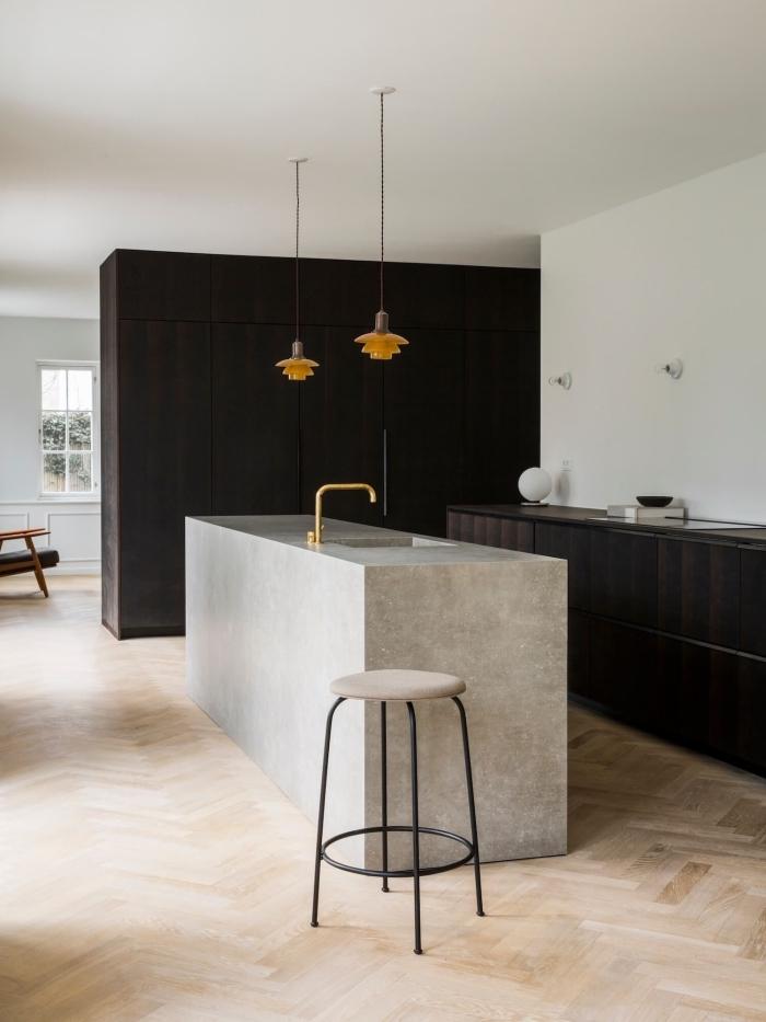 ilot de cuisine en béton ciré avec zone de lavage intégré qui sépare visuellement l'espace de la cuisine ouverte