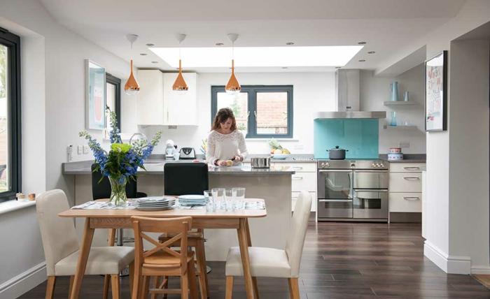 petite cuisine americaine, table basse bois, chaise en bois, bar de cuisine blanc, sol en planches