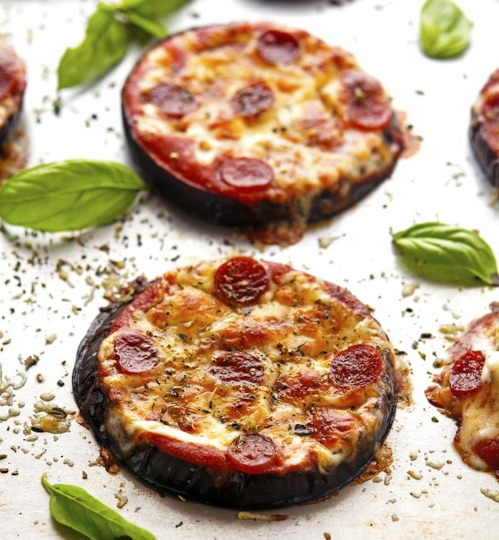 idée de mini pizza avec une base d aubergine rôti au four, avec du fromage et saucisson et sur une sauce marinara