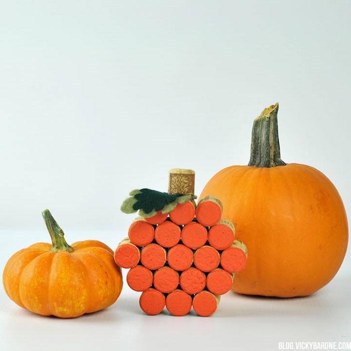 activité manuelle halloween avec des bouchons de liege recyclées, motif citrouille orange et feuilles en feutrine verte
