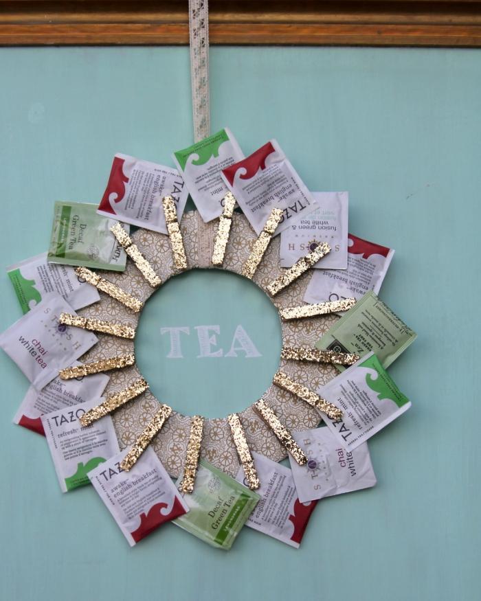 une couronne de noël support de sachets de thé fixés avec des pinces à linges à paillettes, déco murale réalisée avec un objet détourné de son usage traditionnel