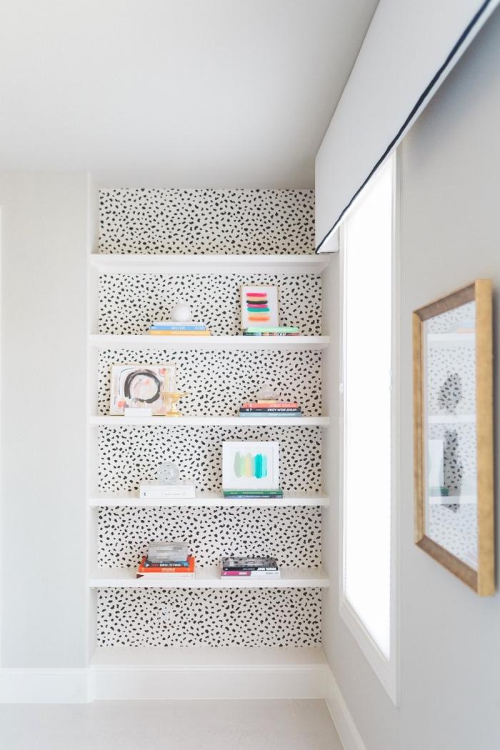 poser du papier peint dans une niche murale pour la mettre en valeur, du papier peint pointillé posé derrière des étagères murales ouvertes posées dans une niche murale