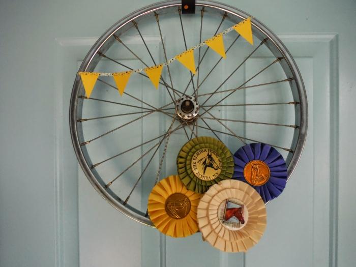 décoration de porte originale avec un objet détourné, roue de vélo recyclée en jolie couronne de porte d'esprit récup