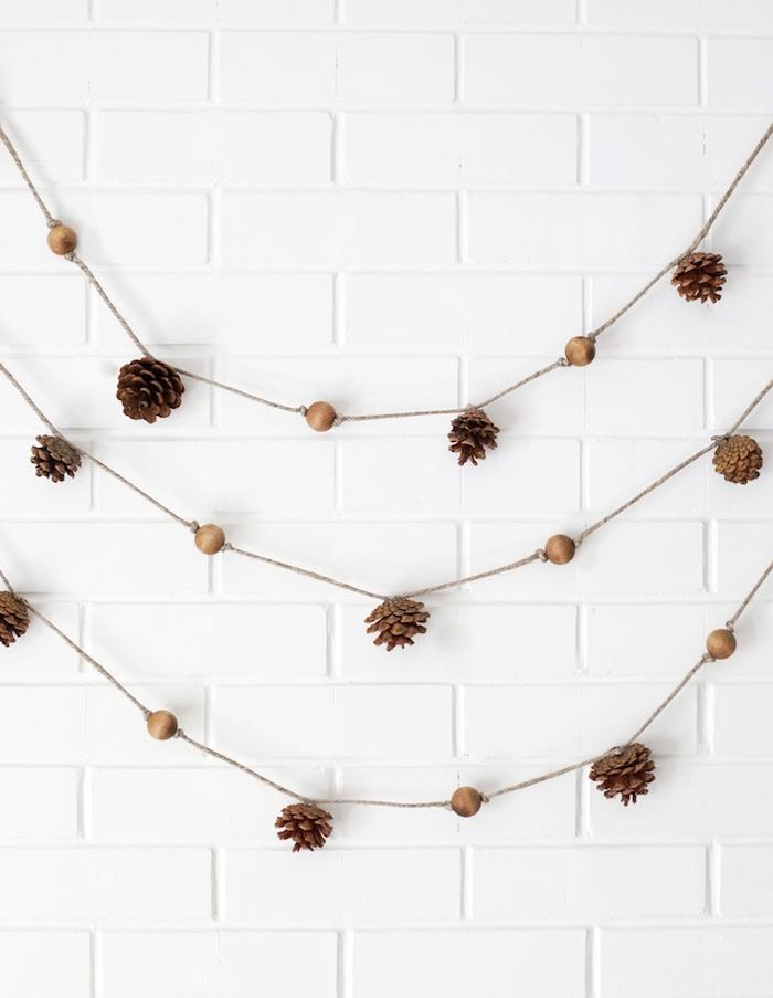 comment faire une guirlande diy en pommes de pin et perles de bois enfilés sur ficelle, deco mur blanc