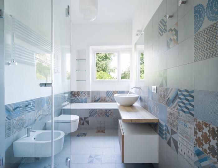 des carreaux de ciment patchwork en tons doux qui recouvrent les murs et le sol de cette salle de bains pleine de douceur et de luminosité
