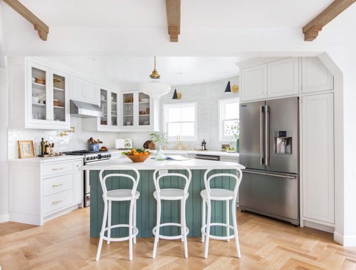 ambiance conviviale et authentique dans une cuisine avec des poutres de bois apparentes au plafond et un ilot de cuisine à façade en lambris peint bleu gris
