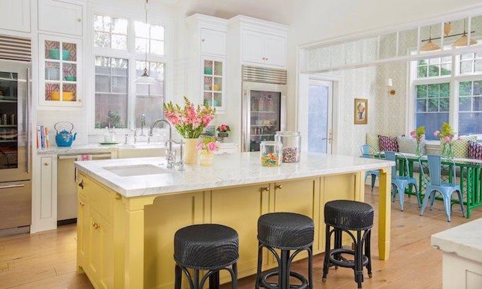 ilot central jaune dans une cuisine campagnarde avec plan de travail marbre, meuble cuisine blanc, coin salle à manger avec des chaises dépareillées