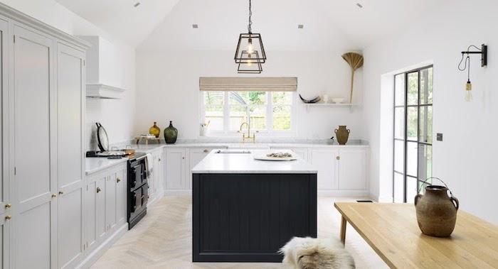 ilot central noir, meuble cuisine bas blanc, suspension industrielle, parquet bois clair, objets rustiques