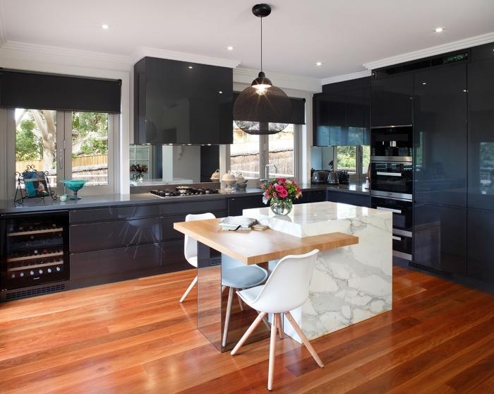 ilot central avec table intégrée qui fait office de desserte et de bar, îlot de cuisine en marbre blanc contrastant avec la finition laquée noire des armoires de cuisine